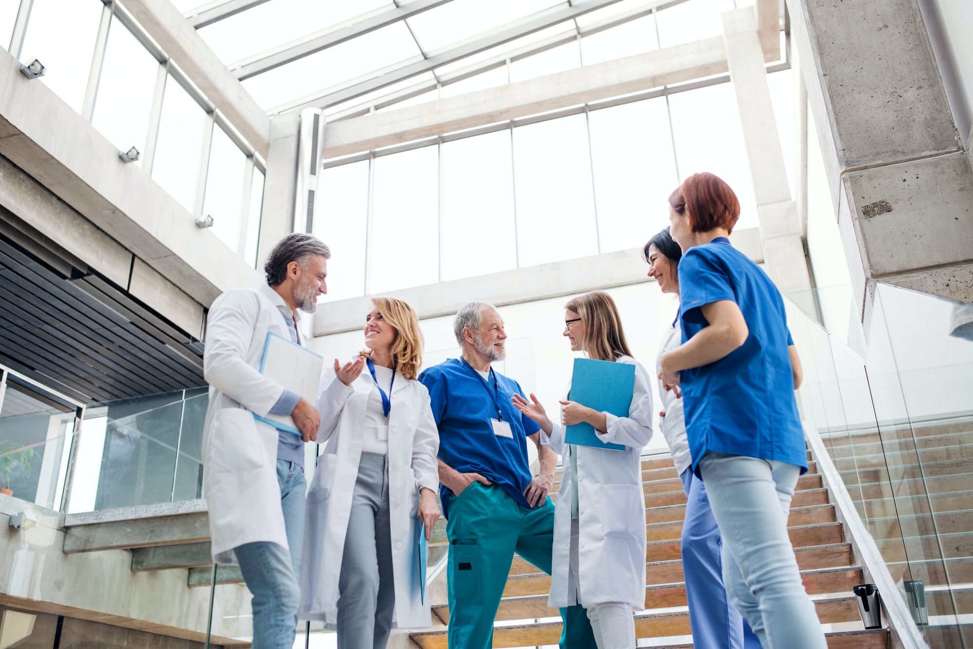 Group of doctors standing on staircase, talking