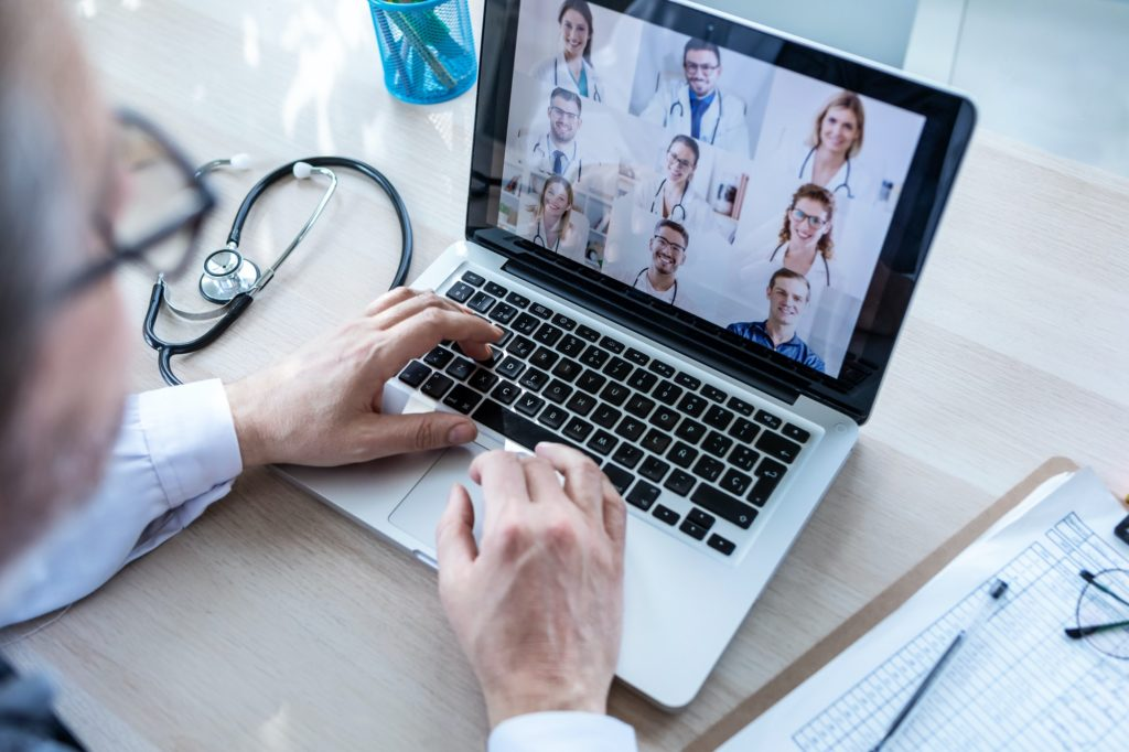 Male doctor having video conference on laptop with his colleagues at home.
