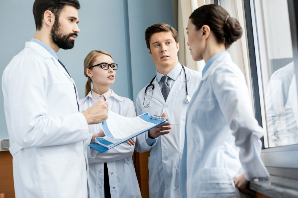 side view of doctors team discussing diagnosis in hospital, caring doctors concept