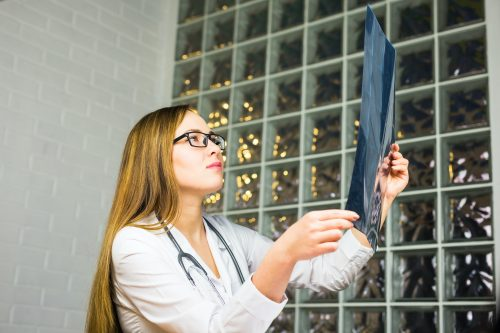 Woman Doctor Looking at X-Ray Radiography in doctor's office